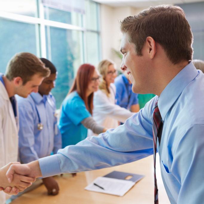 Hospital doctors, nurses, administrators having staff meeting in board room